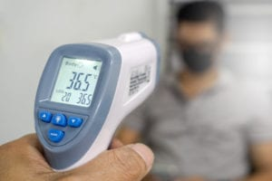 Taking employees temperature with infrared thermometer