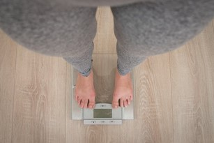 Woman on Scale because of Covid-19 Weight Gain